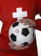 Woman football fan with Swiss flag painted on face, holding football Stock Photos