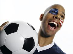 Man with USA flag painted on face, holding football Stock Photos