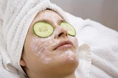 Stock Photo of Young woman with face mask and cucumber slices