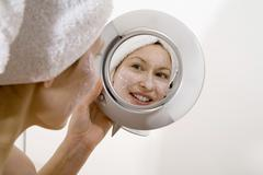 Stock Photo of Young woman applying face mask looking into mirror smiling, close-up