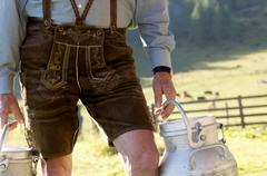 farmer carrying milk cans, midsection - stock photo