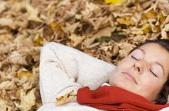 Stock Photo of woman lying on autumn leaves, close-up