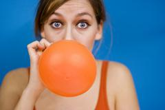 Woman blowing up baloon - stock photo