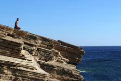 Stock Photo of Greece, Crete, man exercising yoga on cliff