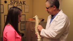 Doctor explains the spine to a female patient. - stock footage