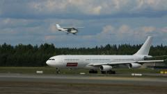 Small Cessna airplane land in front of a huge Airbus A340 Stock Footage