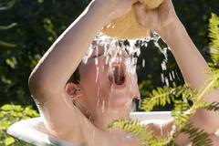 Boy (4-7) playing with sponge in bath tub Stock Photos