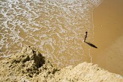 Boy (6-7) on beach, elevated view Stock Photos