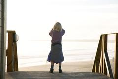 Portugal, Algarve, girl (5-7) standing at beach, rear view Stock Photos