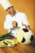 Cook slicing football shaped cabbage Stock Photos