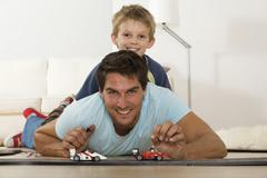 Stock Photo of father and son (6-7) playing with toy cars, smiling, portrait