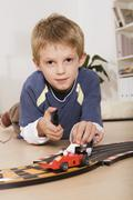 Stock Photo of boy (6-7) playing with toy cars, portrait