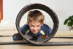 Child (6-7) watching through toy racetrack Stock Photos