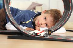 Boy (6-7) playing with toy racetrack, close-up Stock Photos
