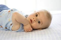 baby boy (6-12 months) lying on back - stock photo