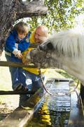 father and son watching pony at fountain - stock photo