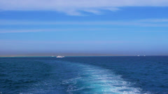 Seascape with azure sea water, wake and land on horizon. - stock footage