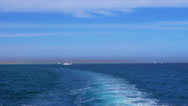 Stock Video Footage of Seascape with azure sea water, wake and land on horizon.