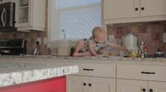 Baby boy and his mother in the kitchen Stock Footage