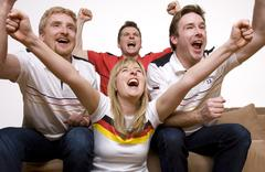 Soccer Fans watching Soccer Game on Television Stock Photos