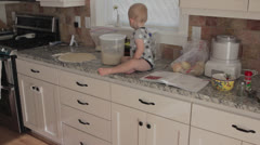 Baby boy helping his mother in the kitchen Stock Footage