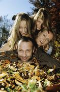Family lying on autumn leafs, close-up, portrait Stock Photos