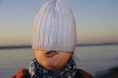 Girl hiding under cap - stock photo
