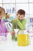 Boy and girl (9-11) in chemical lab, boy pouring liquid Stock Photos