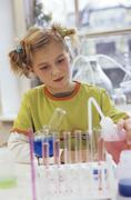 Girl (8-9) doing chemistry experiment - stock photo