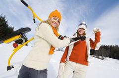woman carrying sledge, friend waving hand - stock photo