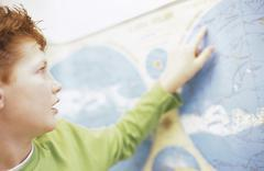 Boy (8-9) pointing at world map - stock photo
