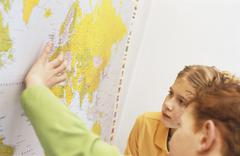 Boy and girl (8-9) looking at world map Stock Photos