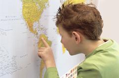 Boy (8-9) looking at world map, close-up Stock Photos