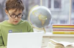 Boy (8-9 years) using laptop - stock photo