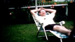 1960s male lounge chair and sits down relaxing summer day vintage relax hot lazy Stock Footage