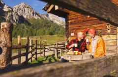 Stock Photo of couple sitting in front of alpine hut