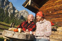 Couple sitting in front of alpine hut Stock Photos