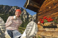 woman in front of alpine hut, holding mug - stock photo