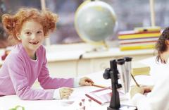 Boy and girl (6-9) sitting by microscope, smiling Stock Photos