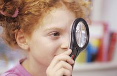 Girl (6-7) looking through magnifying glass, elevated view - stock photo