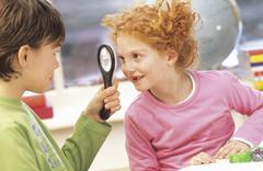 Boy and girl (7-9) fooling around with magnifying glass Stock Photos