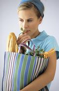 Stock Photo of Woman carrying shopping bag with baguette and vegetable