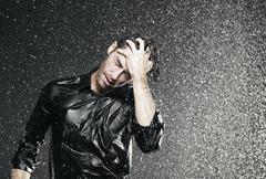 Man standing in rain, head in hand. - stock photo