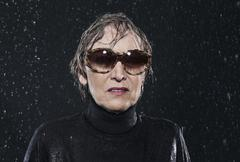 Woman standing in rain, wearing sunglasses. Stock Photos