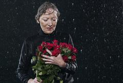 Woman standing in rain, holding bouquet. - stock photo