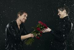 Men offering bouquet to women under rain. Stock Photos