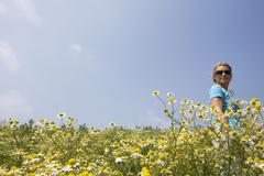 Stock Photo of Woman walking across camomile field