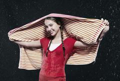 Stock Photo of Girl standing in rain, holding towel.