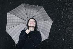 Woman standing in rain, holding umbrella. Stock Photos
