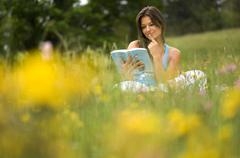 Young woman reading book, sitting in meadow - stock photo